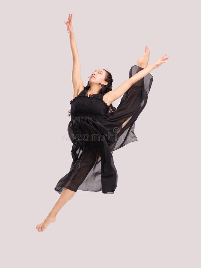 Молодая и талантливая девушка гимнаста скача вверх по распространять ее ноги в шпагате стоковая фотография