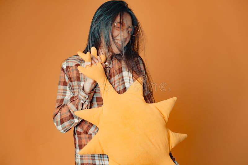 Молодая кавказская девушка брюнета с солнцем игрушки на оранжевой предпосылке стоковые изображения