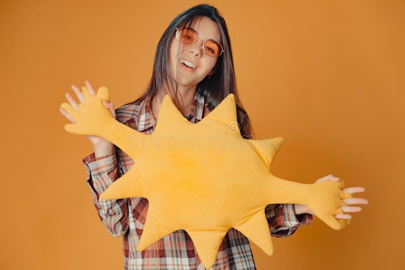 Молодая кавказская девушка брюнета с солнцем игрушки на оранжевой предпосылке стоковое фото rf