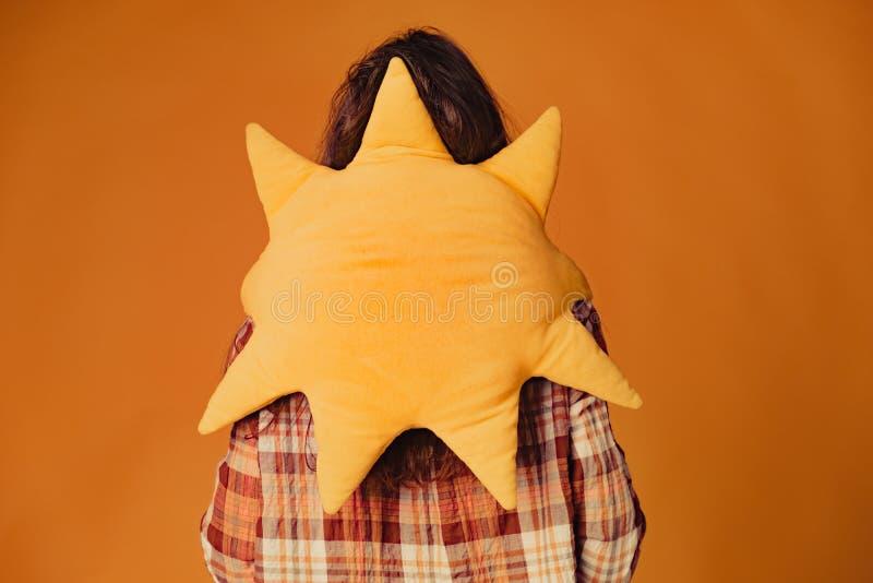 Молодая кавказская девушка брюнета с солнцем игрушки на оранжевой предпосылке стоковая фотография rf