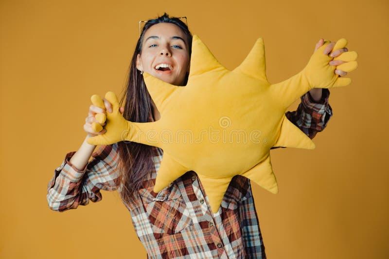 Молодая кавказская девушка брюнета с солнцем игрушки на оранжевой предпосылке стоковые фото