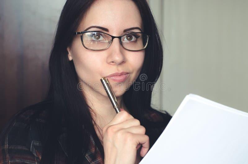Молодая кавказская девушка с стеклами держит ручку и документ и думает стоковая фотография