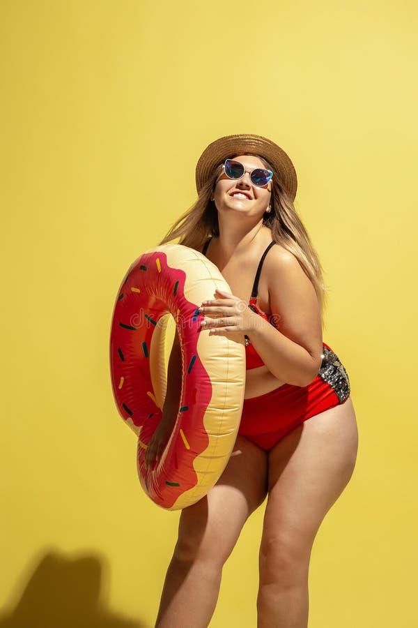 Молодая кавказская женская модель плюс размер готовится к пляжному курорту стоковое фото
