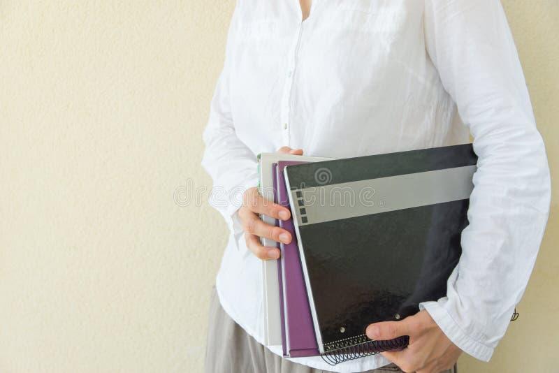 Молодая кавказская женщина в белой рубашке хлопка стоит держащ блокноты workbooks в руках Пустая предпосылка стены Университет ко стоковые фотографии rf