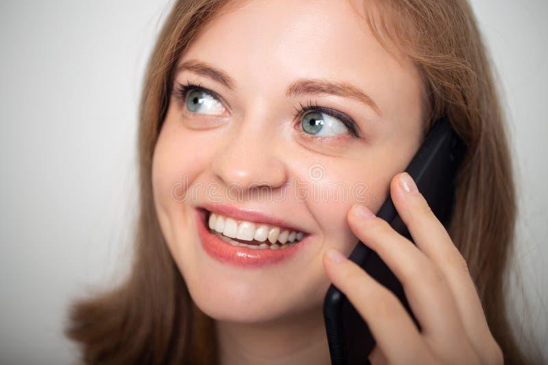 Молодая кавказская женщина девушки говорит на мобильном телефоне и усмехается, конец вверх стоковое фото rf