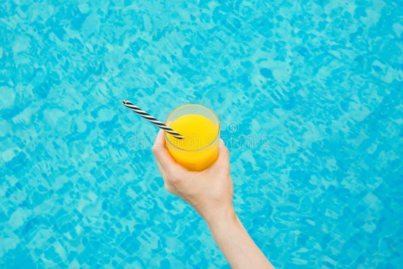 Молодая кавказская женщина держит стекло свеже отжатого апельсинового сока тропических плодоовощей с Striped соломой бассейном стоковое изображение rf