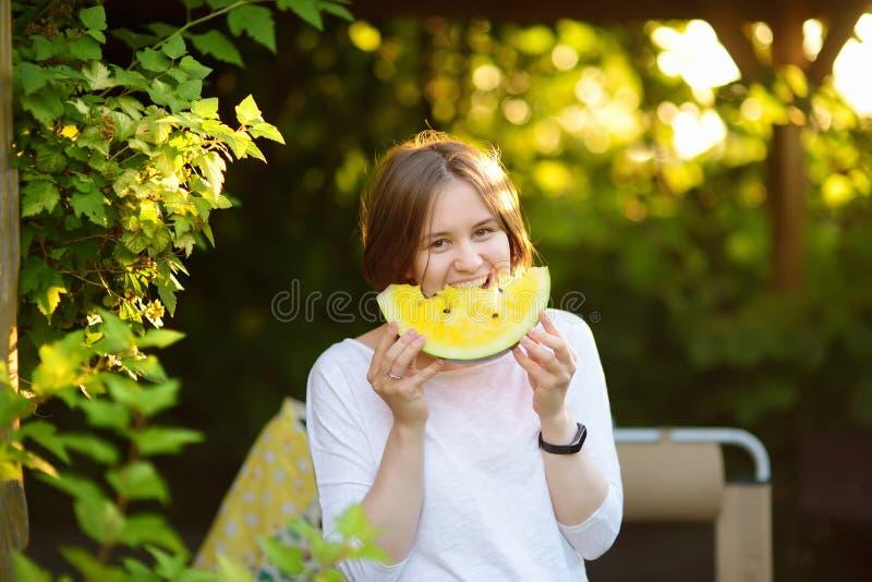 Молодая кавказская женщина есть желтый арбуз outdoors стоковые изображения
