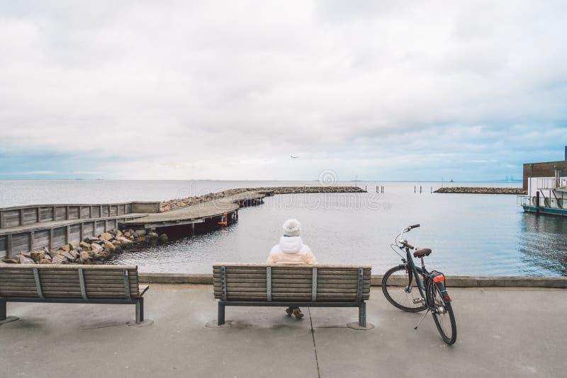 Молодая кавказская женщина сидит с ее задней частью на деревянной скамье обозревая Балтийское море на набережной в Копенгагене Да стоковое фото