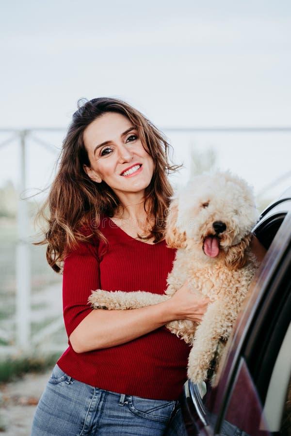 молодая кавказская женщина со своей собакой в машине Концепция поездок Образ жизни и животные стоковые фото