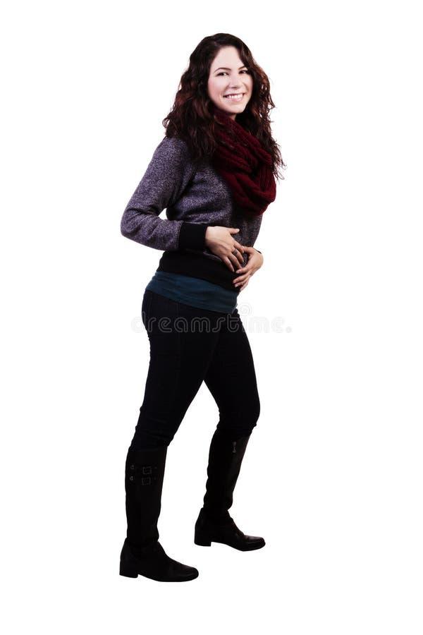 Молодая кавказская женщина стоя в джинсах с улыбкой стоковая фотография