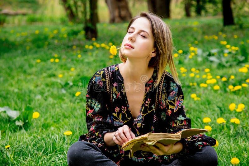 Молодая кавказская женщина с книгой на луге с одуванчиками стоковое изображение