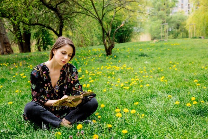 Молодая кавказская женщина с книгой на луге с одуванчиками стоковое фото rf