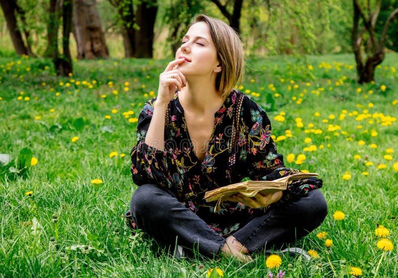 Молодая кавказская женщина с книгой на луге с одуванчиками стоковые изображения
