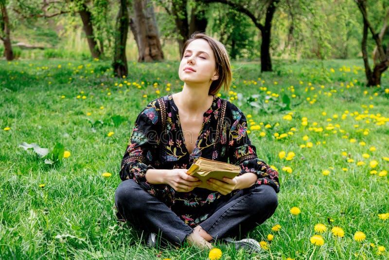 Молодая кавказская женщина с книгой на луге с одуванчиками стоковые фотографии rf