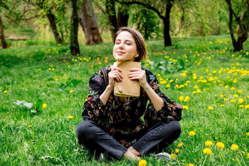 Молодая кавказская женщина с книгой на луге с одуванчиками стоковая фотография rf