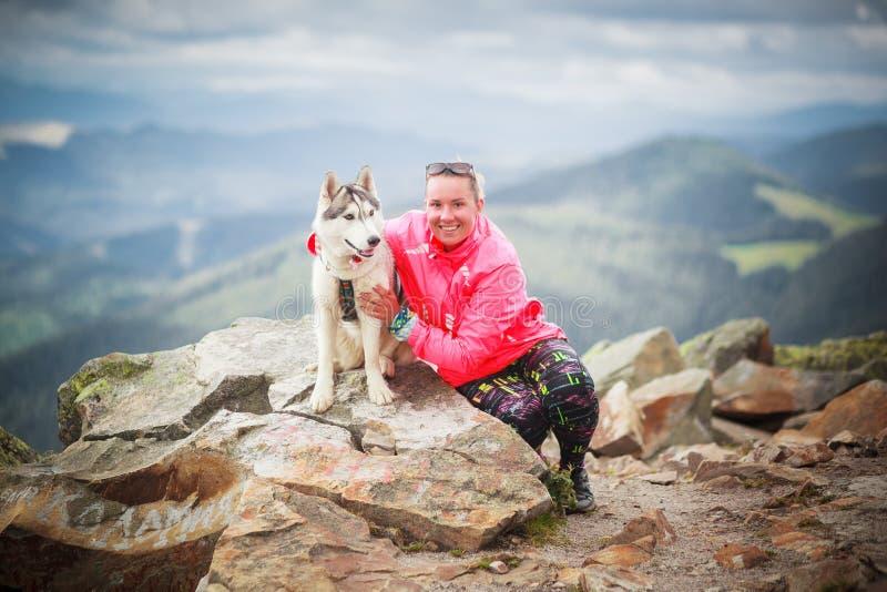 Молодая кавказская женщина с собакой сибирской лайки стоковая фотография rf