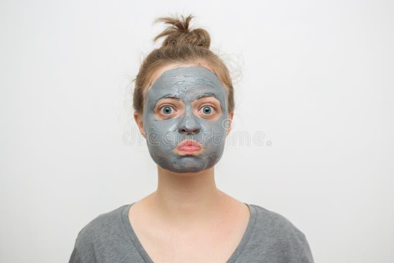 Молодая кавказская женщина с черной или серой лицевой маской глины на ее смешной стороне стоковое изображение rf