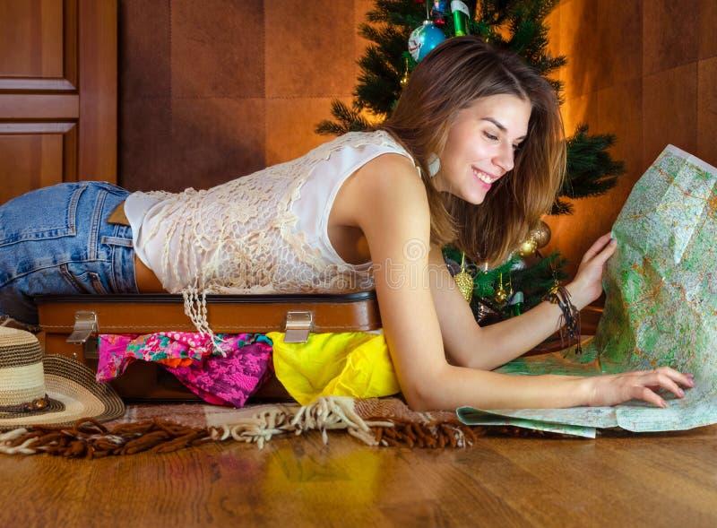 Молодая кавказская женщина, туристская в Новом Годе около рождественской елки жизнерадостная, счастливая, славная улыбка девушки  стоковые изображения