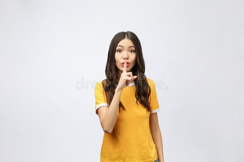Молодая кавказская красивая бизнес-леди над изолированной предпосылкой спрашивая быть тихий с пальцем на губах Безмолвие и стоковая фотография