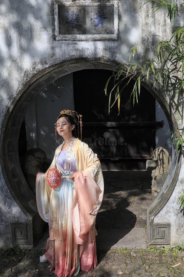 Молодая китайская женщина одела с одеждой традиционного китайския в китайском саде представляя для изображений стоковые изображения