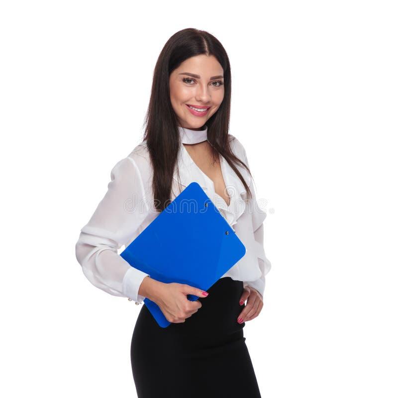 Молодая коммерсантка брюнет держа голубую доску сзажимом для бумаги стоковые изображения rf