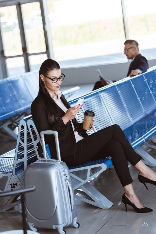 молодая коммерсантка в стеклах с багажем используя смартфон стоковая фотография