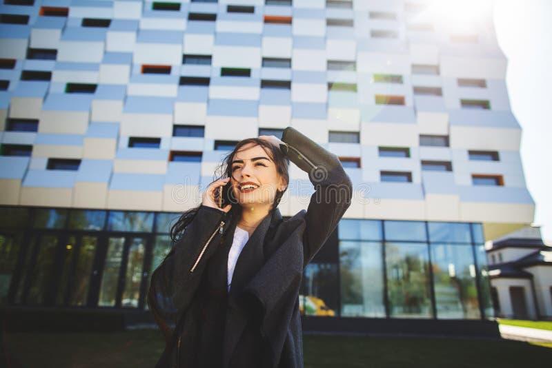 Молодая коммерсантка говоря на мобильном телефоне во время на открытом воздухе перерыва на чашку кофе, около офисного здания E стоковые изображения rf