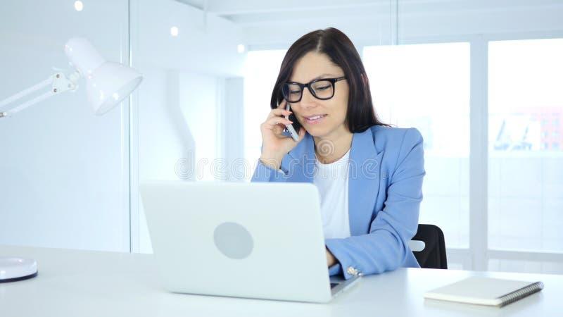 Молодая коммерсантка говоря на телефоне, присутствуя на звонке на работе стоковые изображения