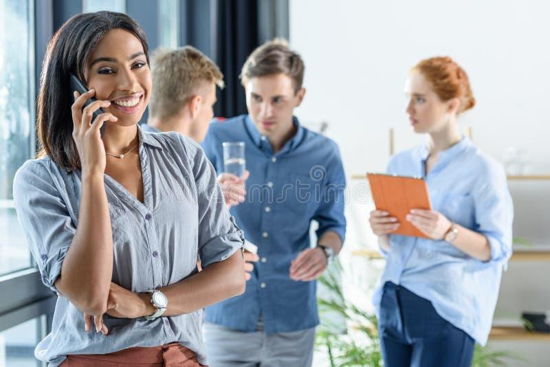 Молодая коммерсантка говоря на smartphone пока команда дела обсуждая проект в современном стоковое фото