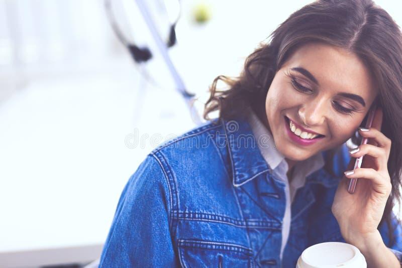Молодая коммерсантка говоря по телефону в кофейне стоковые изображения