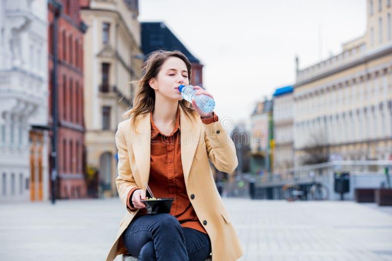Молодая коммерсантка есть салат и питьевую воду стоковые изображения