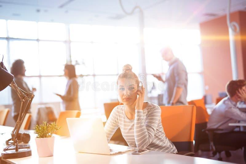 Молодая коммерсантка используя компьютер на работе стоковые изображения