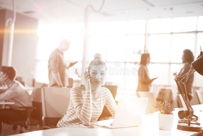 Молодая коммерсантка используя компьютер на работе стоковое фото