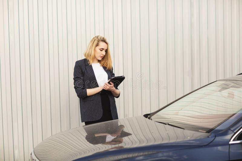 Молодая коммерсантка используя планшет, во время на открытом воздухе перерыва на чашку кофе, около офисного здания E стоковое изображение rf