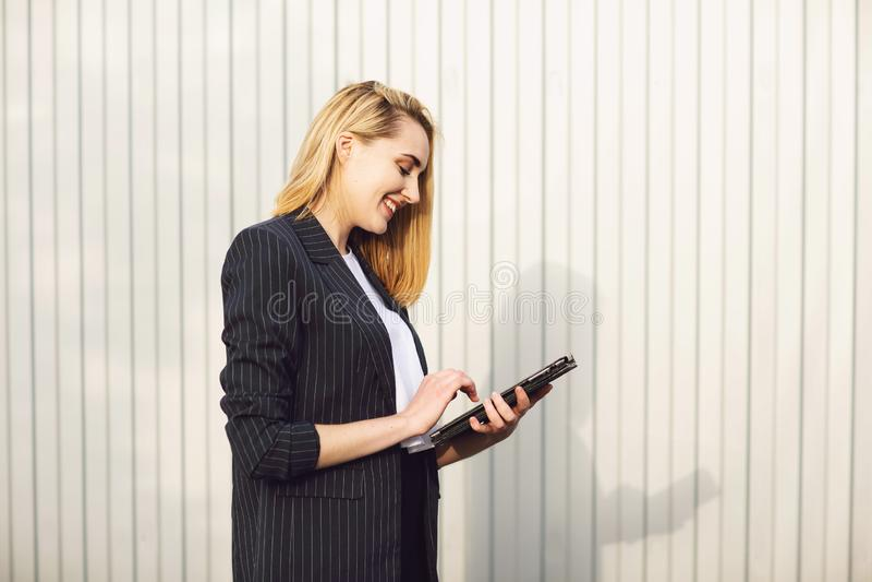 Молодая коммерсантка используя планшет, во время на открытом воздухе перерыва на чашку кофе, около офисного здания E стоковое изображение