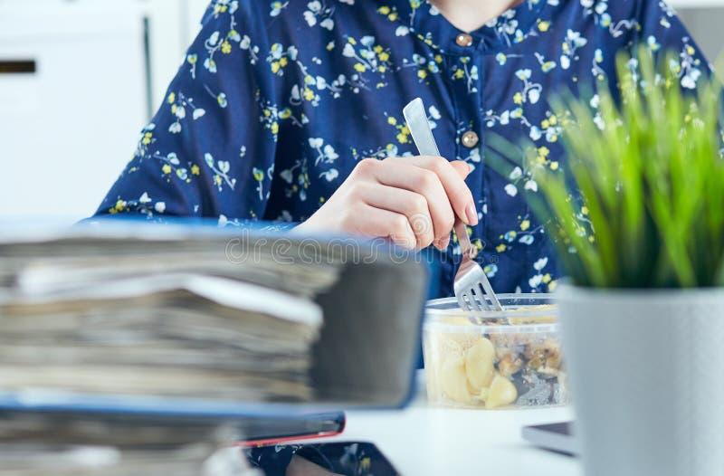 Молодая коммерсантка сидя в офисе с компьтер-книжкой используя беспроволочный интернет, имеющ обед стоковые фотографии rf