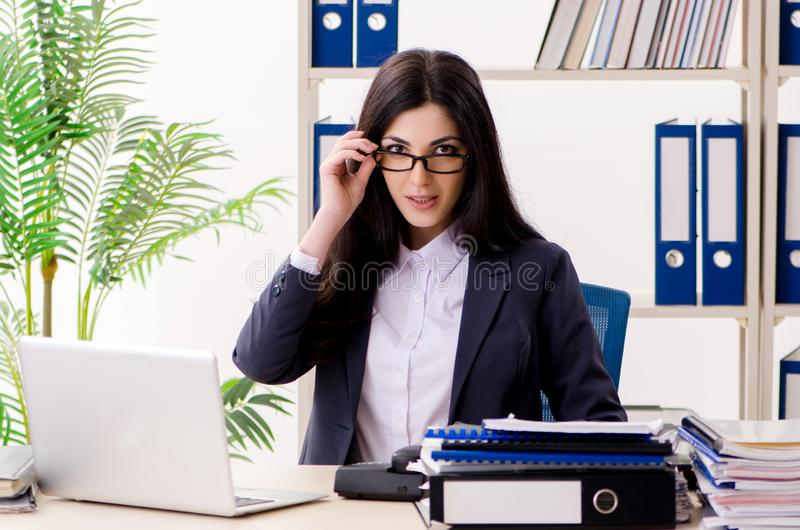 Молодая коммерсантка сидя в офисе стоковые фотографии rf