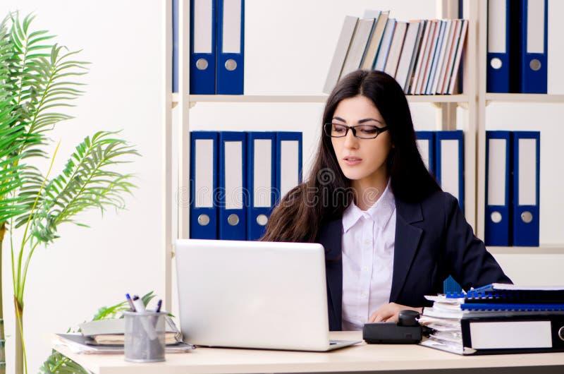 Молодая коммерсантка сидя в офисе стоковые изображения rf