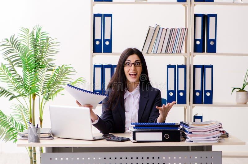 Молодая коммерсантка сидя в офисе стоковое фото rf