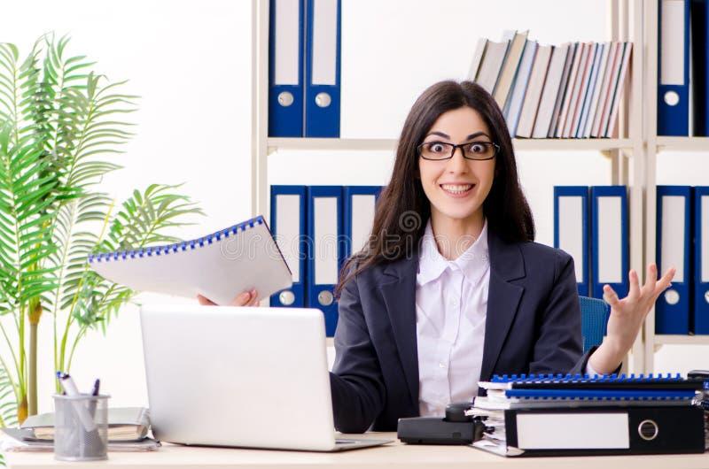 Молодая коммерсантка сидя в офисе стоковые изображения