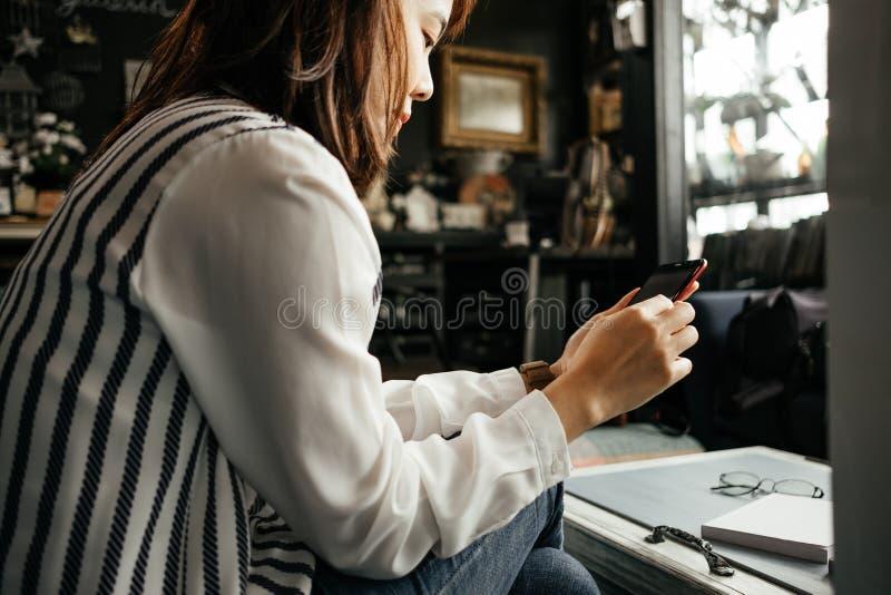 Молодая коммерсантка сидя в рабочем месте и используя мобильный телефон стоковые изображения