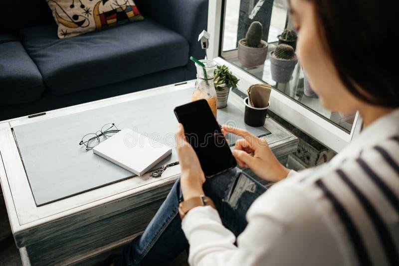 Молодая коммерсантка сидя в рабочем месте и используя мобильный телефон стоковая фотография rf