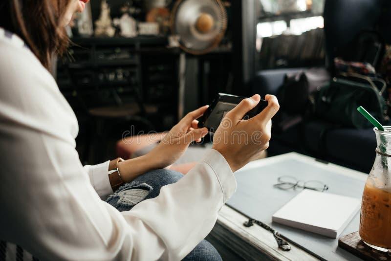 Молодая коммерсантка сидя в рабочем месте и используя мобильный телефон стоковое фото