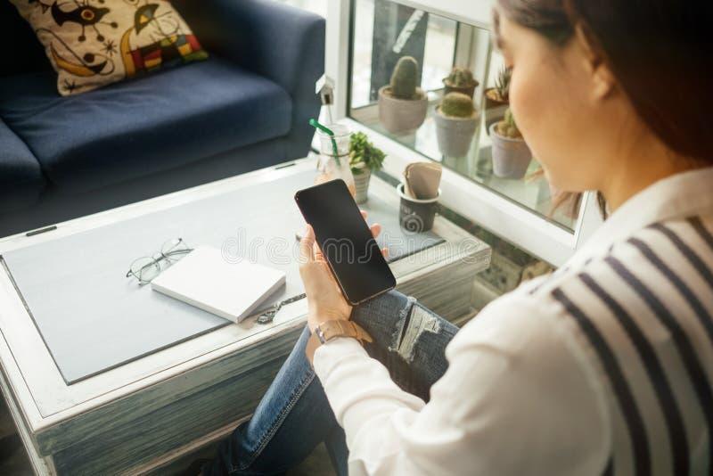 Молодая коммерсантка сидя в рабочем месте и используя мобильный телефон стоковые фото