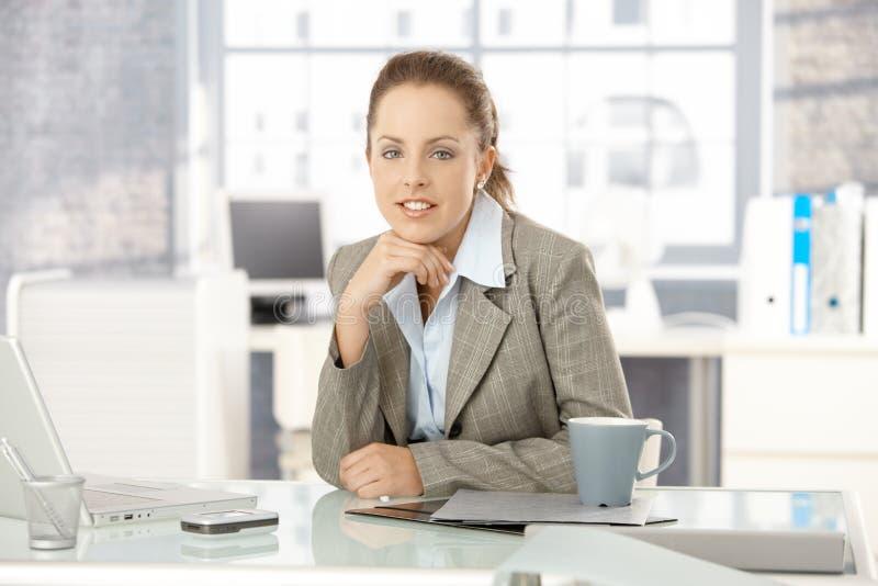 Молодая коммерсантка сидя в ярком офисе стоковое изображение rf