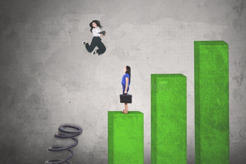 Молодая коммерсантка скача над ее соперником стоковое изображение