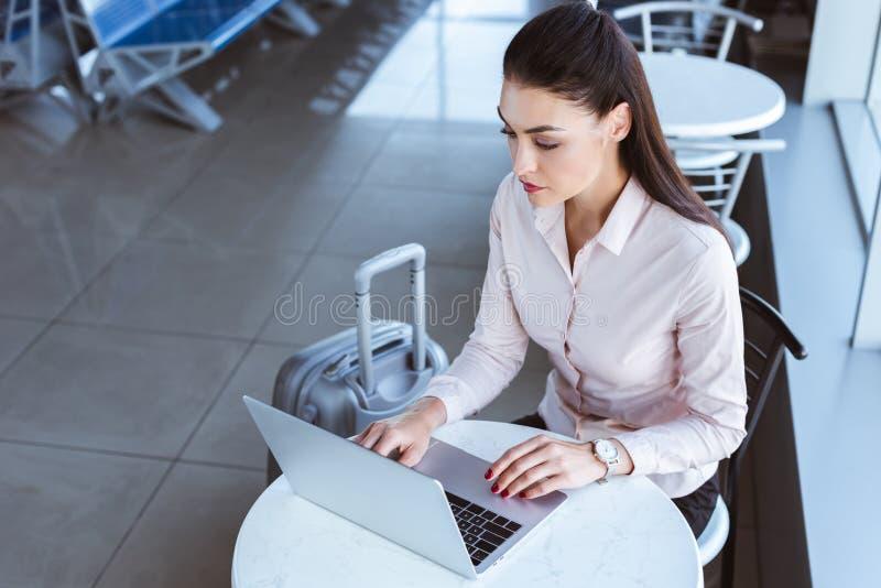 молодая коммерсантка с багажом используя ноутбук стоковые фото