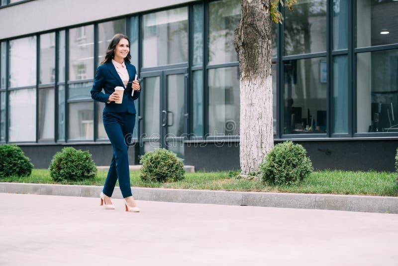 молодая коммерсантка с идти кофе и тетради стоковые фото