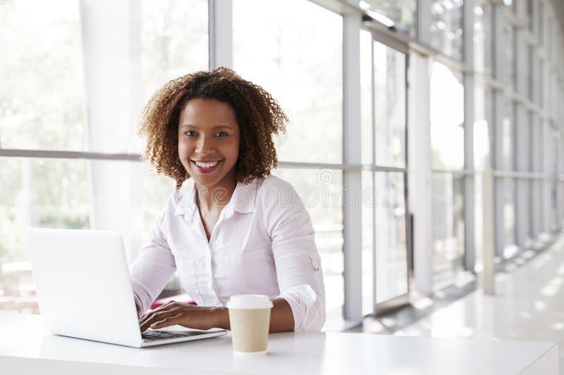 Молодая коммерсантка с компьтер-книжкой на столе смотря к камере стоковая фотография rf