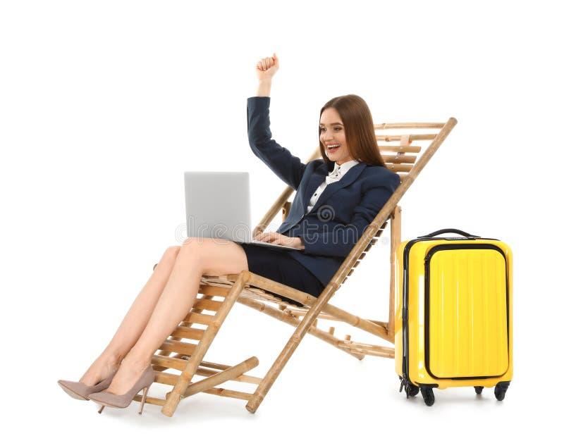 Молодая коммерсантка с ноутбуком и чемоданом на шезлонге против белой предпосылки стоковые фото